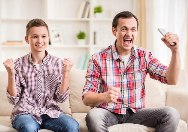 Pai e filho que sentam-se junto e que olham o fósforo de futebol.