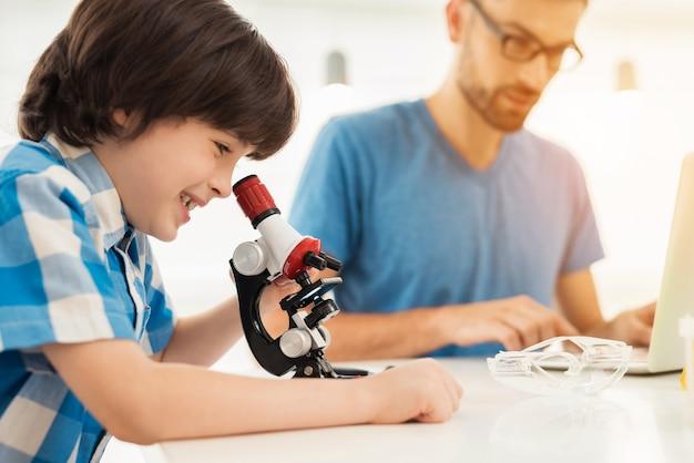 Pai e filho realizam experimentos químicos em casa.