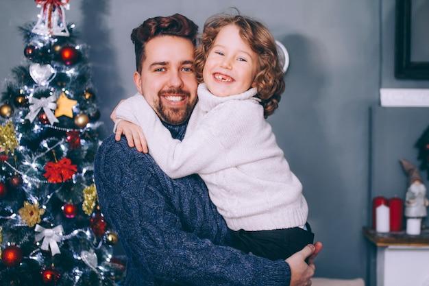 Pai e filho se abraçam na árvore de natal. uma criança feliz e seu pai estão olhando para o quadro.