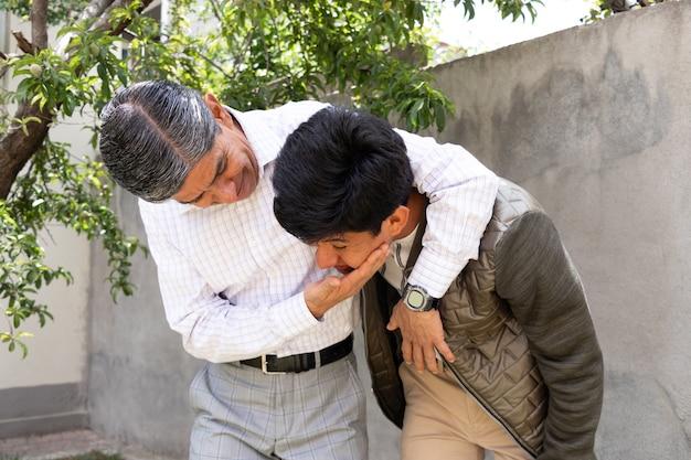 Pai e filho se abraçando, brincando e rindo no jardim