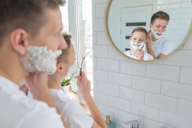 Pai e filho se barbeando no espelho do banheiro