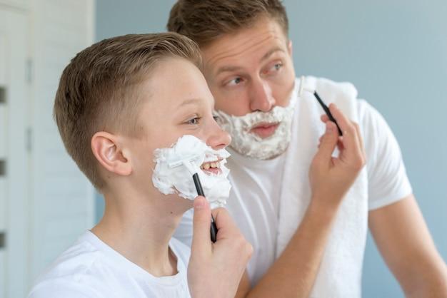 Pai e filho se barbeando no espelho