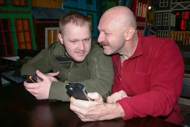 Pai e filho se comunicam sentados à mesa e estudam informações nos telefones