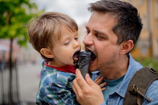 Pai e filho se divertem com sorvete preto ao ar livre