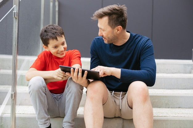 Pai e filho se divertem discutindo um novo jogo usando o tablet enquanto estão sentados em degraus de concreto na cidade