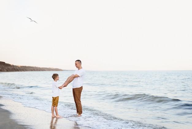 Pai e filho se divertindo na costa do mar. férias em família. amizade