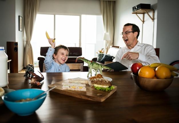 Pai e filho se divertindo na mesa de café da manhã