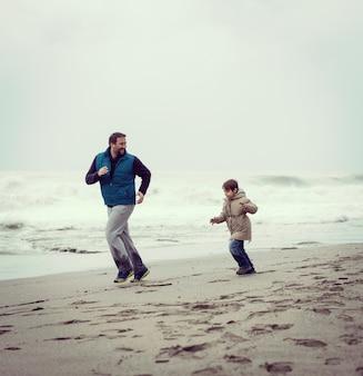 Pai e filho se divertindo na praia de inverno