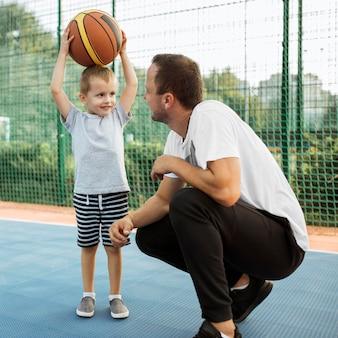 Pai e filho se divertindo no campo de basquete