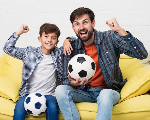 Pai e filho segurando bolas de futebol