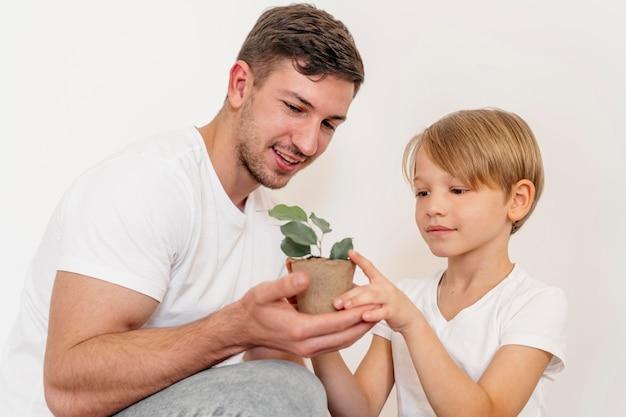 Pai e filho segurando um vaso de planta e aprendendo sobre como plantar