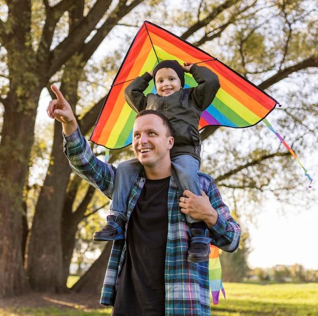 Pai e filho segurando uma pipa no parque