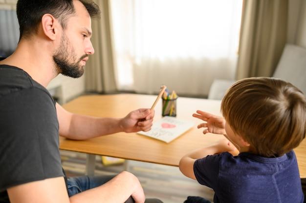Pai e filho sentado à mesa