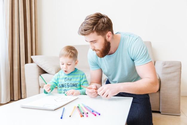 Pai e filho sentados e desenhando na sala de estar em casa