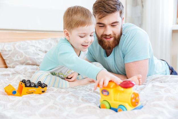 Pai e filho sentados na cama brincando com brinquedos em casa