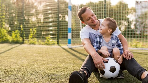 Pai e filho sentados no campo de futebol