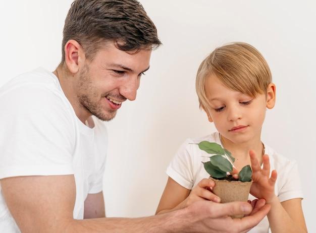 Pai e filho sorridente segurando um vaso de planta
