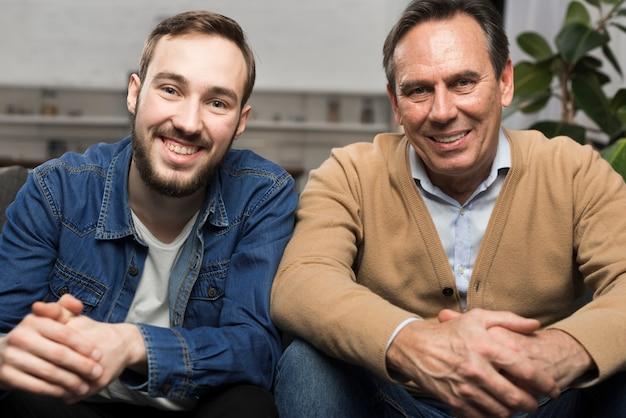 Pai e filho sorrindo e posando na sala de estar