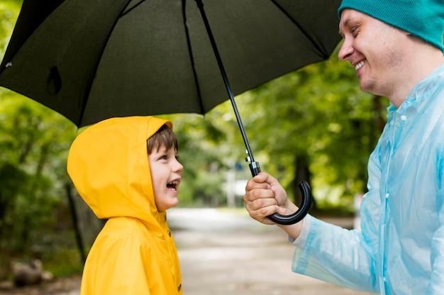 Pai e filho sorrindo um para o outro sob o seu guarda-chuva