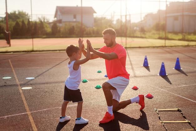 Pai e filho tempo. pai orgulhoso no campo de treinamento com seu filho