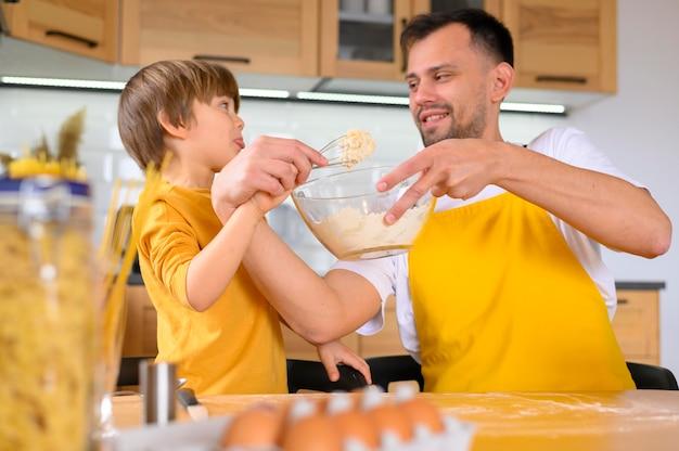 Pai e filho tentando fazer uma massa