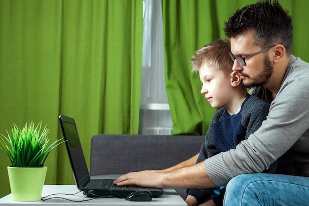 Pai e filho trabalhando em um laptop.