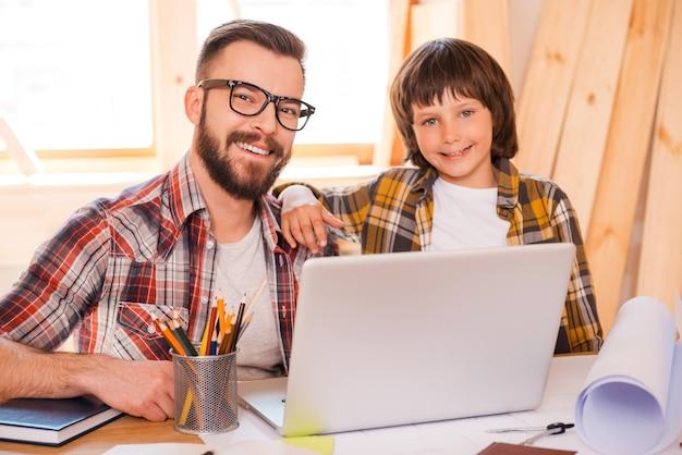 Pai e filho trabalhando juntos. jovem alegre trabalhando em um laptop com seu filho enquanto está sentado no local de trabalho