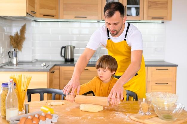 Pai e filho usando a raquete na cozinha
