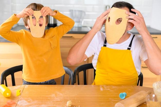 Pai e filho usando máscaras de massa