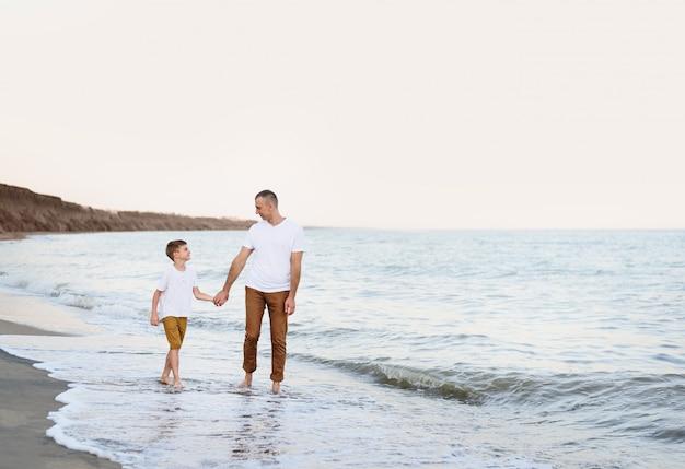 Pai e filho vão pela mão ao longo da costa do mar