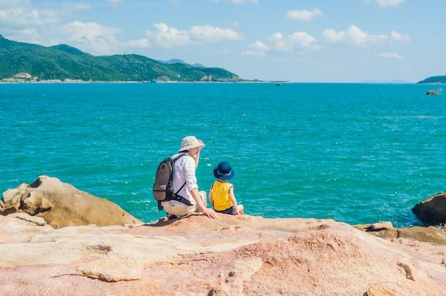 Pai e filho viajantes na capa de hon chong, pedra de jardim, destinos turísticos populares em nha trang. vietnã