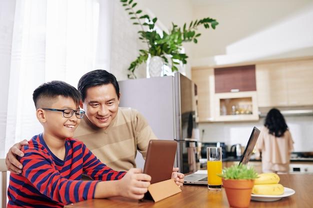 Pai e filho vietnamitas alegres assistindo a um vídeo educacional no computador tablet enquanto a mãe prepara o jantar