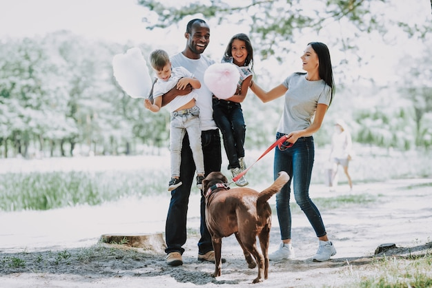 Pai e filhos brincam no parque família feliz e cachorro.