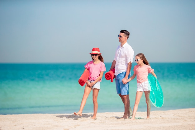 Pai e filhos caminhando na praia de areia branca