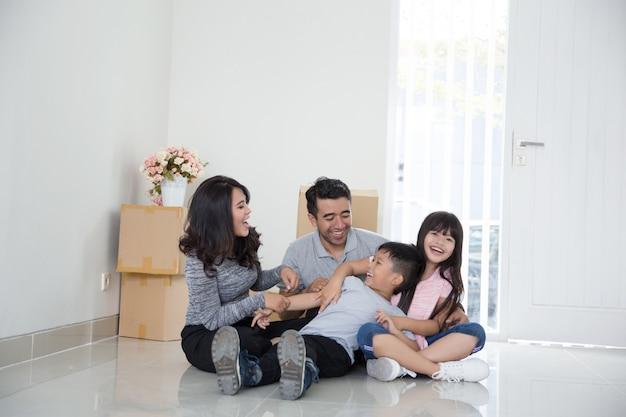 Pai e filhos com caixa de papelão. mudar para casa nova