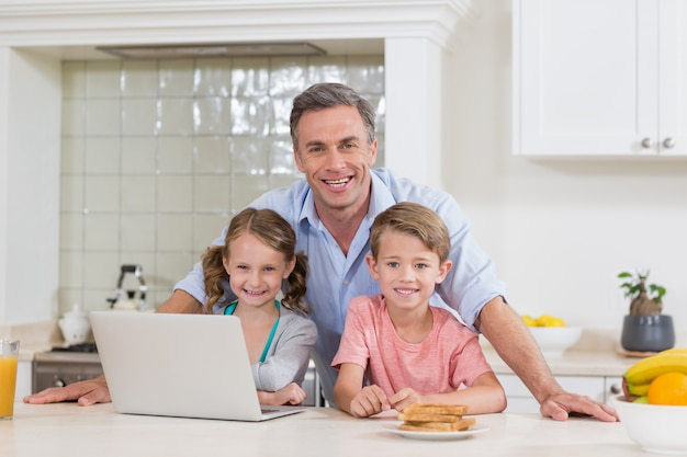 Pai e filhos com o laptop na cozinha