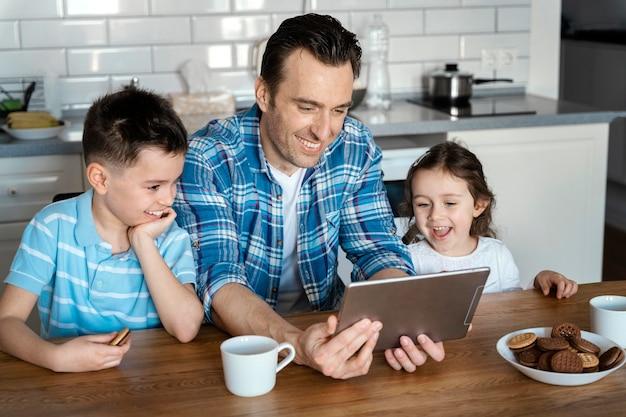 Pai e filhos com tiro médio com tablet