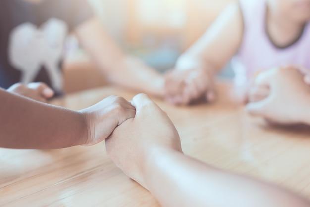 Pai e filhos de mãos dadas e rezando juntos na mesa de madeira