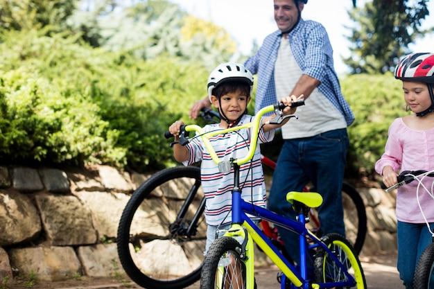 Pai e filhos em pé com bicicleta no parque