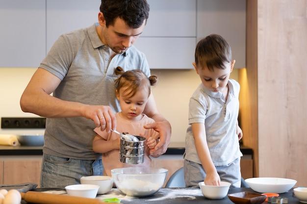 Pai e filhos em tiro médio na cozinha