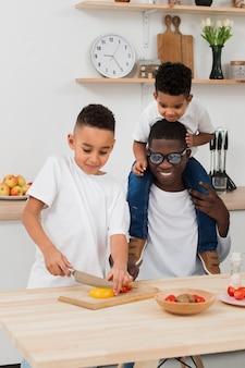Pai e filhos juntos a preparar o jantar