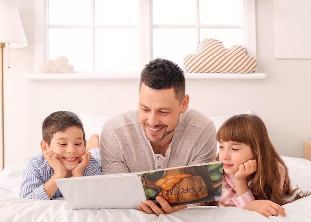 Pai e filhos pequenos lendo histórias para dormir em casa