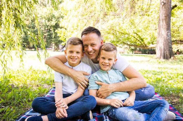 Pai e filhos posando enquanto olha para a câmera