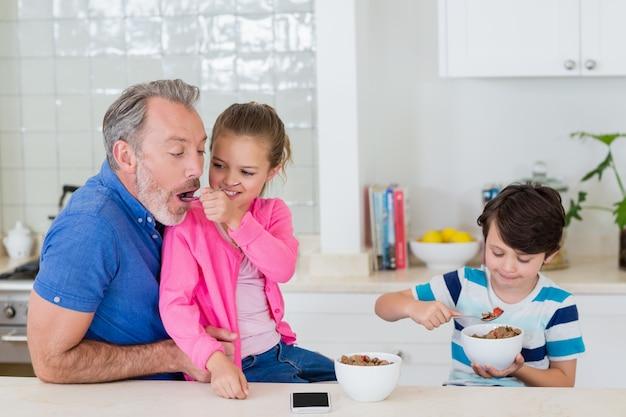 Pai e filhos tomando café na cozinha