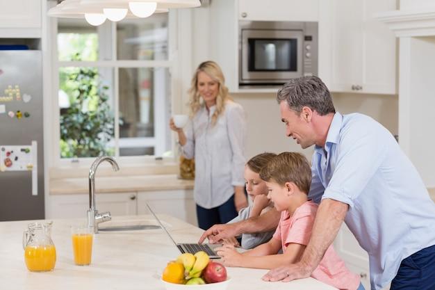 Pai e filhos usando laptop enquanto tomando café da manhã
