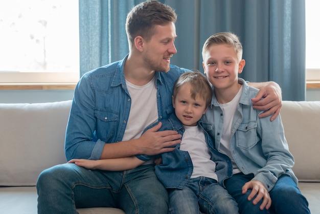 Pai e irmãos bonitos, sentado no sofá