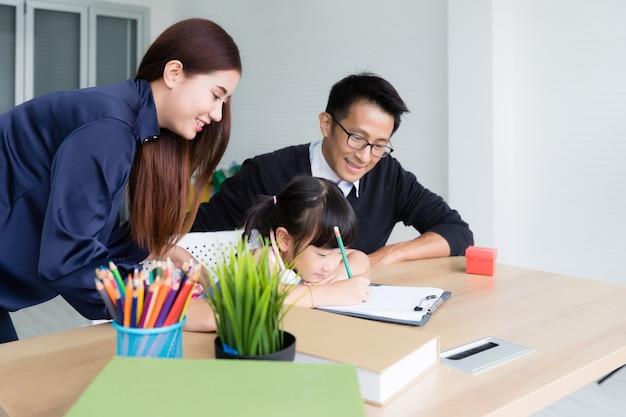 Pai e mãe asiáticos ensinando lição de casa à filha