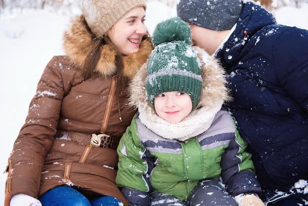 Pai e mãe caminham com o filho pequeno em uma floresta no inverno.