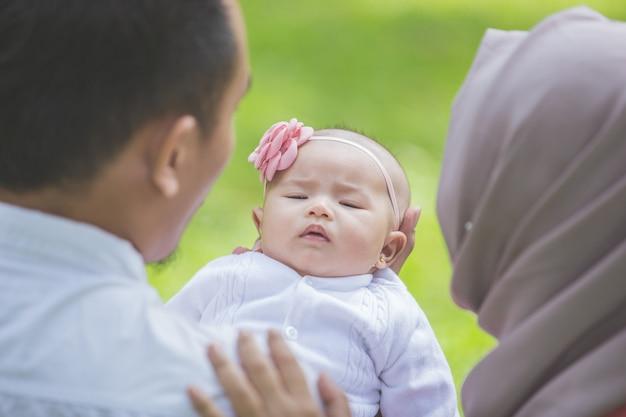 Pai e mãe com seu bebê recém-nascido no parque.