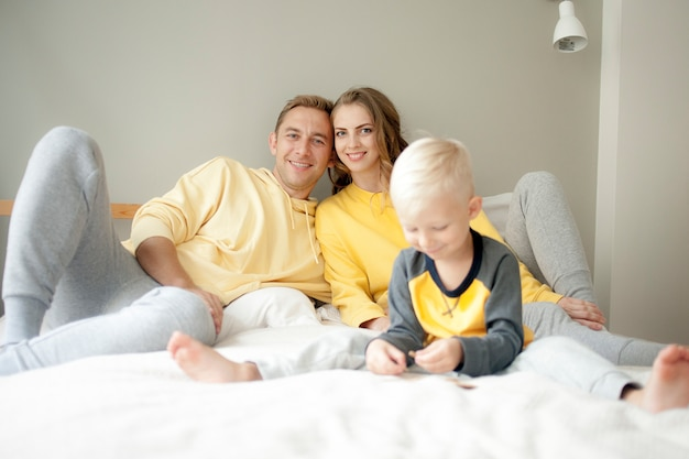 Pai e mãe de família jovem brincam com o filho na cama